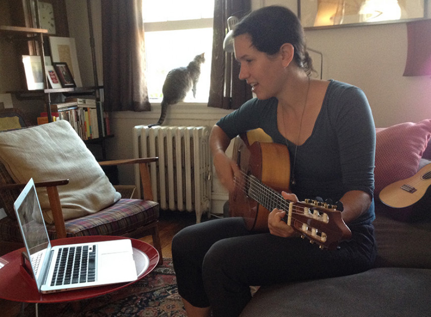 Leah with guitar on computer with cat