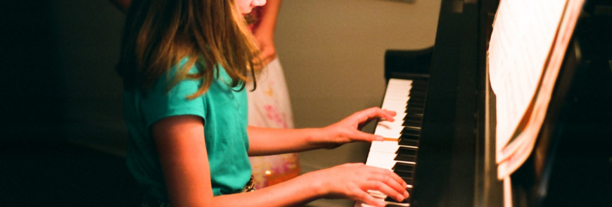 Children reading music on a piano